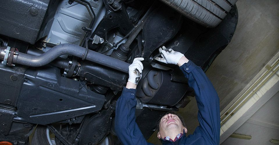 Auto Mechanic working undernieth car